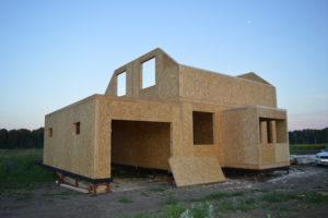 Фото строительства недорогого, каркасного дома из СИП панелей с гаражом по готовому проекту на этапе монтажа 2 этажа (Новосибирск, Томск, Барнаул, Алтай, Новокузнецк)